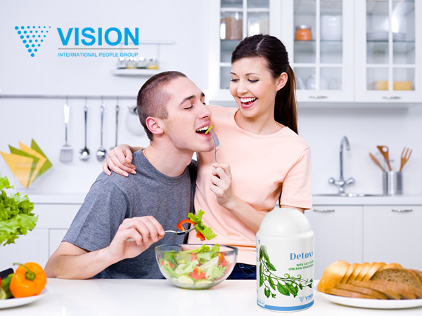Happy playful young couple eating together in the kitchen